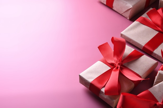 Символы влюбленности поздравительной открытки предпосылки дня валентинки, красное украшение с коробками подарков на розовой предпосылке. вид сверху с копией пространства и текста. плоская планировка