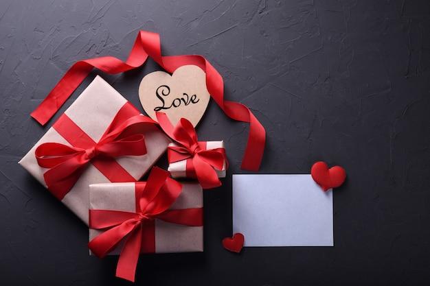 Символы влюбленности поздравительной открытки предпосылки дня валентинки, красное украшение с коробками подарков на каменной таблице. вид сверху с копией пространства и текста. плоская планировка