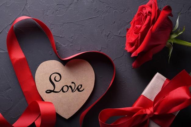 Символы влюбленности поздравительной открытки предпосылки дня валентинки, красное украшение с подарками роз сердца стекел на каменной таблице. вид сверху с копией пространства и текста. плоская планировка