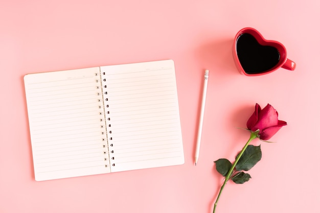 Valentine's day background. heart shaped cup of black coffee, red rose and notebook on pastel pink