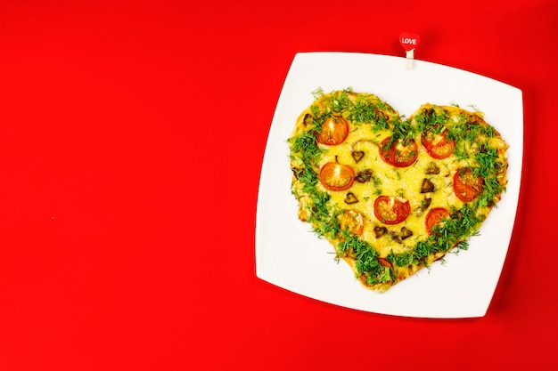 Valentine's day background.  heart shaped pizza, on a white plate, on a red background