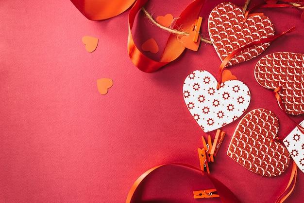 バレンタインデーの背景。ハート、赤いリボン、ピンクのパステルカラーの洗濯バサミ。