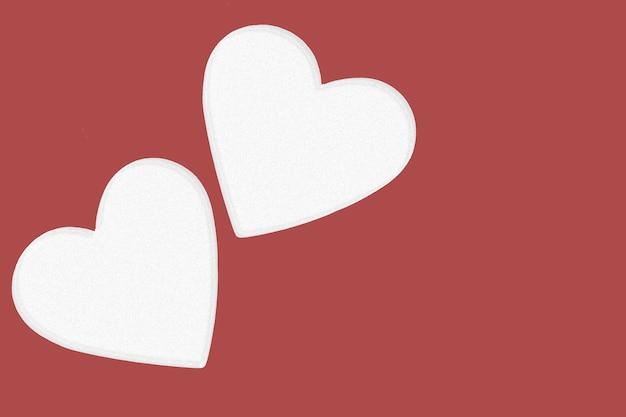 バレンタインデーの背景。愛のカード。結婚式のコンセプト。赤い背景に2つのハート。スペースをコピーします。