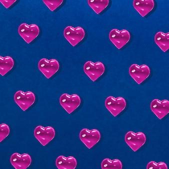 バレンタインデーの背景。青にピンクのガラスのハートのパターン