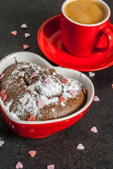 バレンタインデーの背景、赤いコーヒーのマグカップとチョコレートのマグカップケーキ、または粉砂糖と甘いハートのブラウニー型の振りかける、黒の背景、コピースペース