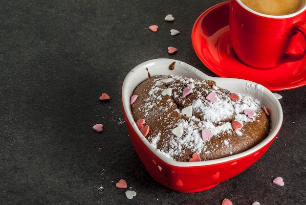 Valentine's day background, red coffee mug and chocolate mug cake or brownie with powdered sugar and sweet heart shaped sprinkles, black background, copy space