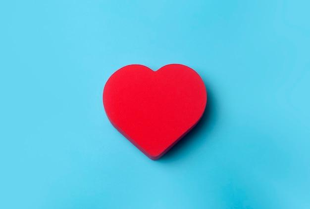 День святого валентина фон. красное сердце на синем минимальном фоне. концепция любви, романтики и сердца.