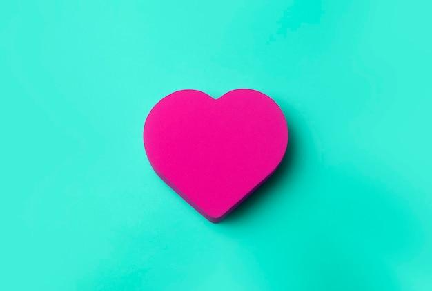 День святого валентина фон. красное сердце на зеленом минимальном фоне. концепция любви, романтики и сердца.