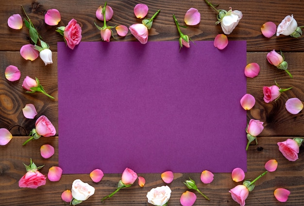 Valentine's day background. round frame floral pattern  made of pink and beige roses, green leaves on wooden background. flat lay, top view.