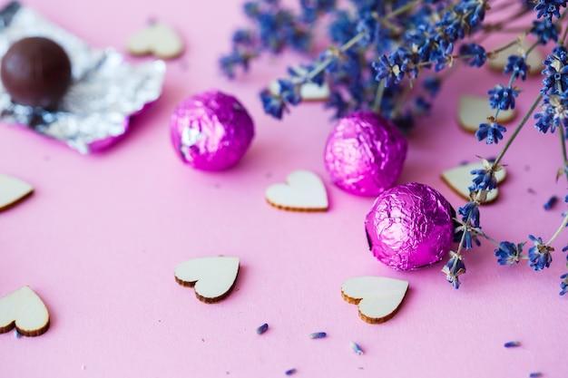 발렌타인의 날 배경입니다. 분홍색 배경에 나무 하트 줄, 마른 라벤더 가지의 측면 보기. 발렌타인 데이 개념입니다. 상위 뷰, 비문, 광고 장소