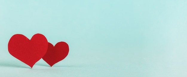 Valentine's day background. two red paper hearts on pastel blue background with copy space