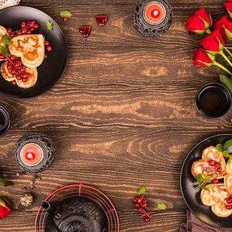 Valentine's day background with delicious pancakes in form of heart, green tea, black teapot