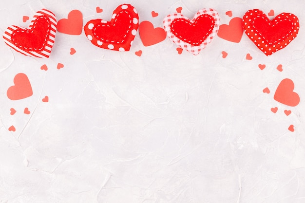Valentine's day background with frame from handmade textile and confetti hearts