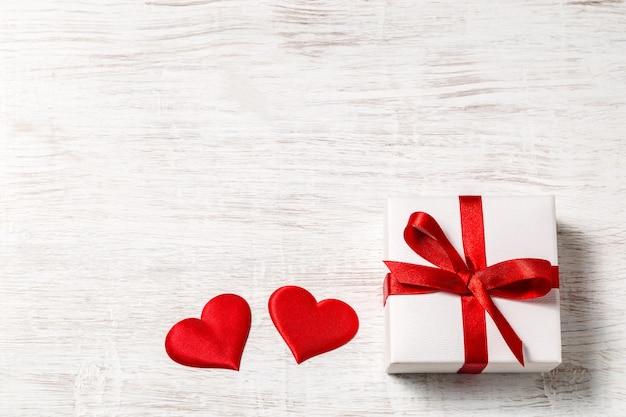 Предпосылка дня валентинки с подарком и красными сердцами, взглядом сверху. сан валентин и понятие любви.
