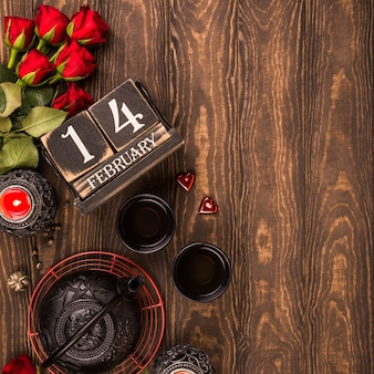 Valentine's day background with green tea, black teapot, candles, roses and wooden calendar