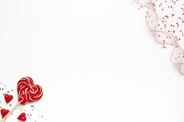 ハートのロリポップ、紙吹雪、白い背景の上のリボンとバレンタインデーの背景