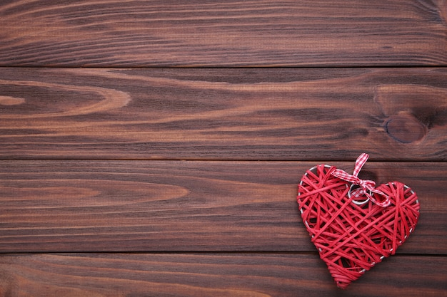 Valentine's day background with red heart on a brown wooden table