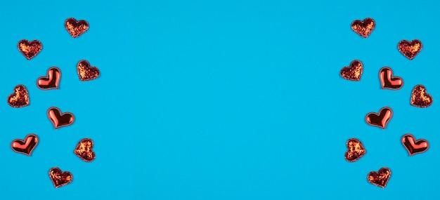 青い背景に赤いハートとバレンタインデーの背景。テキストのフレーム。