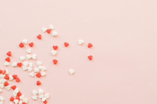 Valentine's day background with red and white little hearts on pink backdrop.