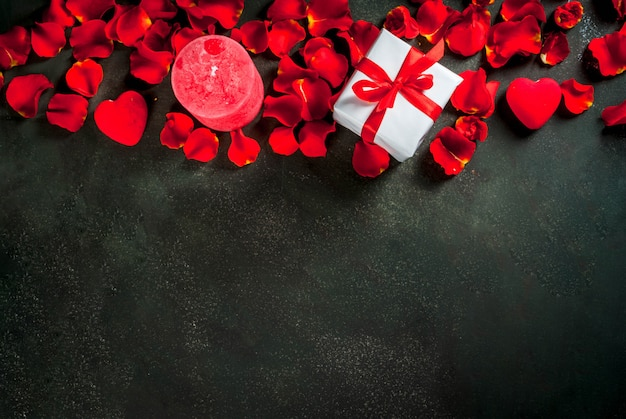 Valentine's day background with rose flower petals, white wrapped gift box with red ribbon and holiday red candle, on dark stone background, copy space top view