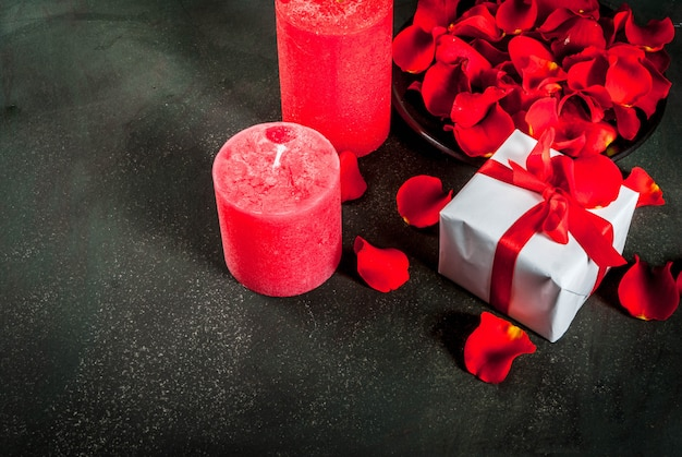 Valentine's day background with rose flower petals, white wrapped gift box with red ribbon and holiday red candle, on dark stone background, copy space