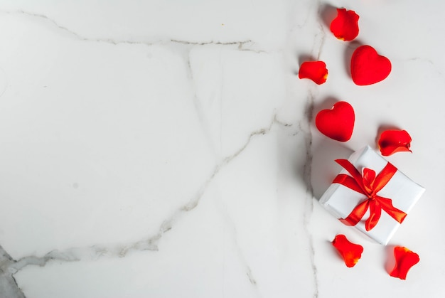Valentine's day background with rose flower petals, white wrapped gift box with red ribbon and holiday red candle, on white marble background, copy space top view