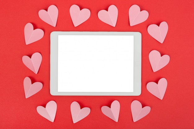 Valentine's day background with touchpad and paper hearts. flat lay.