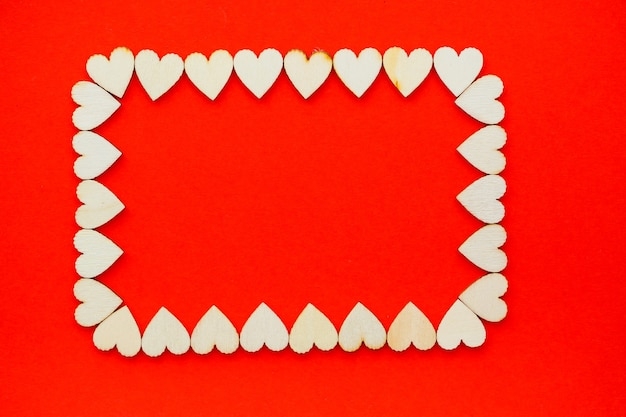 バレンタインデーの背景。木製のハートは、ハートのテキストの場所と赤い背景に長方形で裏打ちされています。はがきのハート。