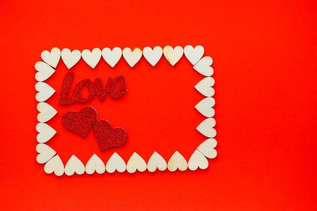 День святого валентина фон. деревянные сердечки выложены прямоугольником на красном фоне с местом для текста с сердечками. сердечки для открыток.