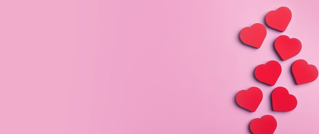 Valentine's day banner background. red hearts on a pink minimal background. love, romance and hearts concept.