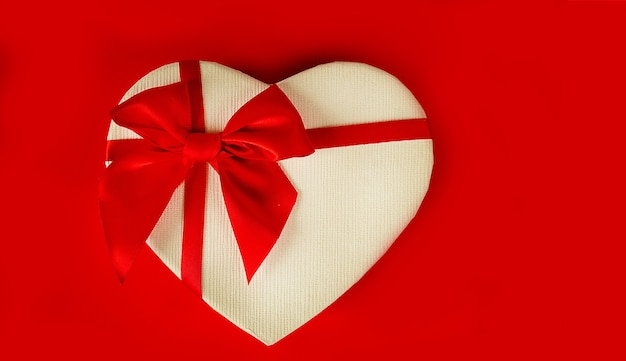 Valentine's day banner. gift box in the form of a heart with a red bow on a white table. international womens day, 8 marc.