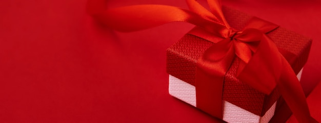Valentine's day banner. gift box with festive ribbon and hearts on the red.
