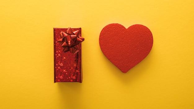 バレンタインデーのバナー、ペーパーアートスタイル。黄色い紙にハートとギフト