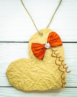 Красивые сердечки на день святого валентина из блестящей бумаги с красным бантом на деревянном белом