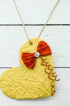 バレンタインの日木製の白に赤の弓と光沢のある紙から作られた美しい心