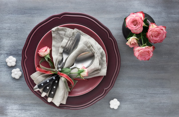 Valentine's day, birthday or anniversary table setup, top view on grey background