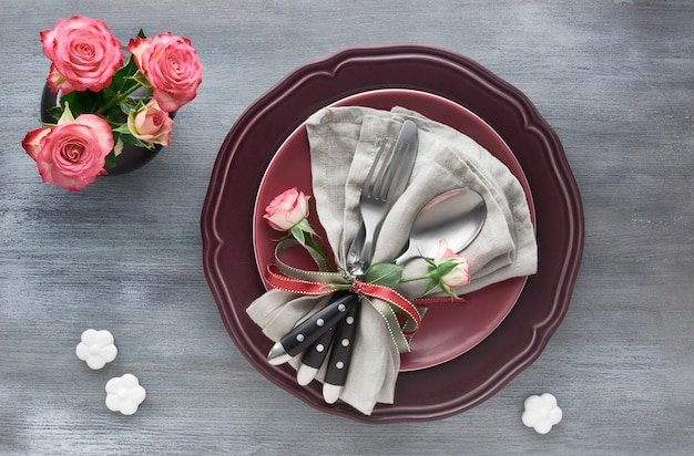 Valentine's day birthday or anniversary table setup, top view on grey. pink roses, dark red plates, napkin and crockery, decorated with rose bud and ribbons.