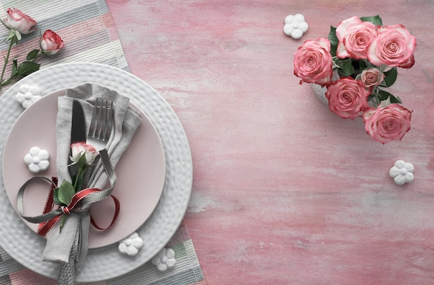 Valentine's day, birthday or anniversary table setup, top view on light pink , copy-