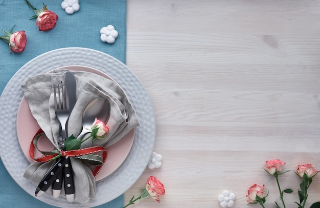 Valentine's day, birthday or anniversary table setup, top view on light rustic table, copy-space