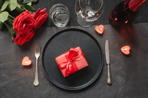 Valentine's day or birthday dinner. elegance table setting with red rose on black linen tablecloth.