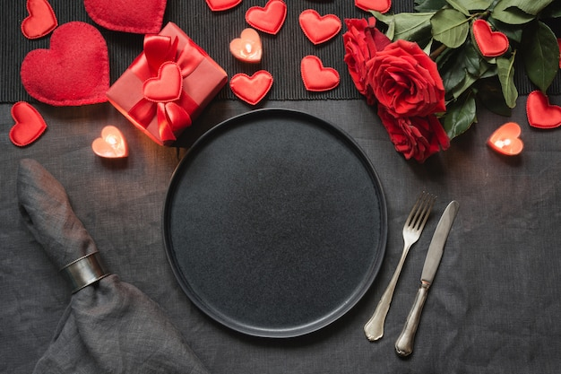 Valentine's day or birthday dinner. romantic table setting with red rose on black linen tablecloth.