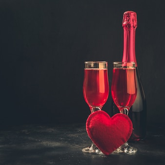 Valentine's day and birthday greeting card with champagne and heart on black.