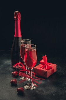 Valentine's day and birthday greeting card with champagne and heart candy on black.