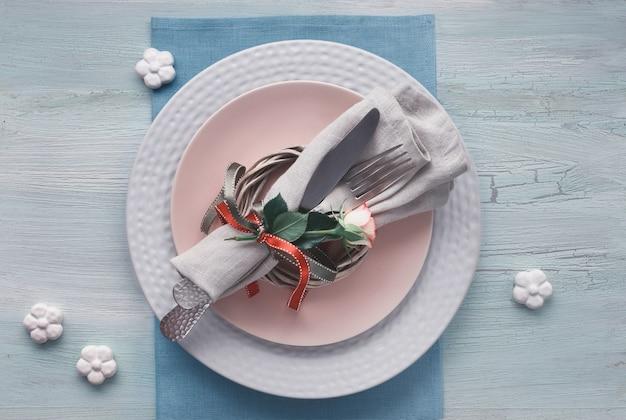발렌타인 데이, 생일 또는 기념일 테이블 설정, 밝은 질감 배경에 상위 뷰. 장미 꽃 봉오리와 리본, 세라믹 꽃과 분홍색 장미로 장식 된 냅킨과 그릇