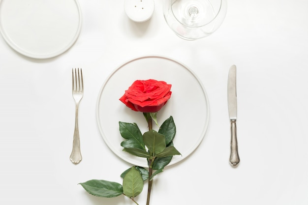 Valentine's day or birthday romantic dinner. elegance table setting with red rose.