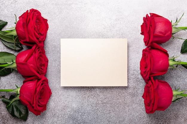 Пустая открытка ко дню святого валентина с цветами красных роз на каменном фоне
