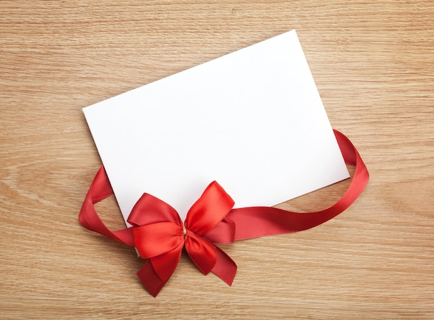발렌타인 데이 빈 선물 카드와 나무 배경에 활이 있는 빨간 리본