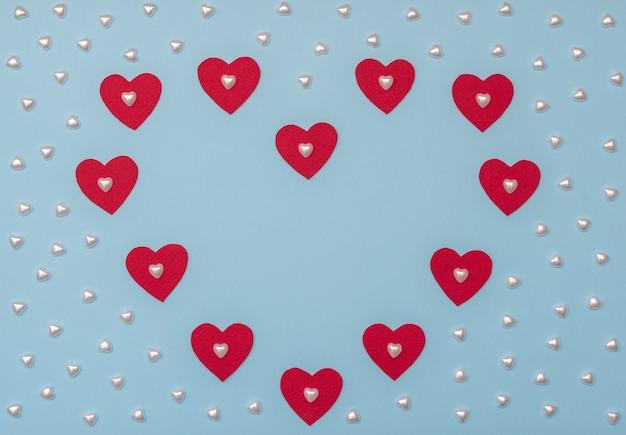 赤と真珠の心とバレンタインデーの青い背景。バレンタイングリーティングカード。コピースペースのあるフラットレイスタイル。