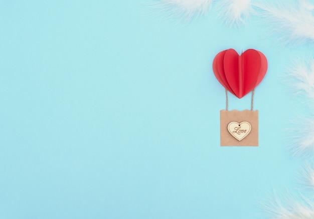 バレンタインデーの青い背景に赤いハートの風船、木製のハートと白い羽のバスケットが付いています。バレンタイングリーティングカード。コピースペースのあるフラットレイスタイル。愛、幸福、結婚式のコンセプト