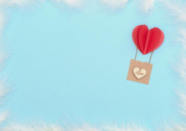 バレンタインデーブルー、赤いハートの風船、木製のハートと白い羽のバスケットが付いています